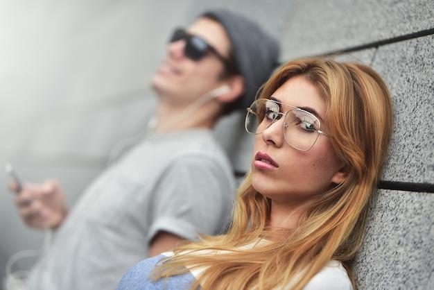 灰色の壁を背景にスタイリッシュな服を着て、同じヘッドフォンで音楽を聴いている若い魅力的なカップルの肖像画。