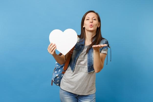 파란색 배경에 격리된 공기 키스를 보내는 복사 공간이 있는 하얀 마음을 들고 배낭을 메고 있는 매력적인 젊은 여성 학생의 초상화. 대학에서 교육입니다. 광고 공간을 복사합니다.