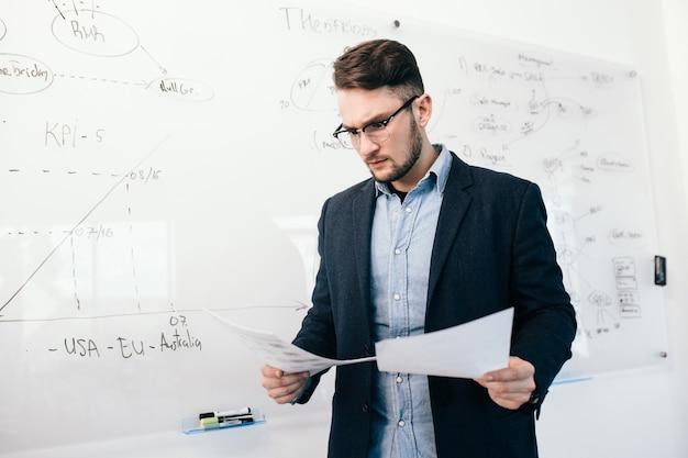 オフィスでドキュメントをチェックするメガネの若い魅力的な暗い髪の男の肖像画。彼は計画を立てて白い机の近くに立っています。彼はジャケット付きの青いシャツを着ています。