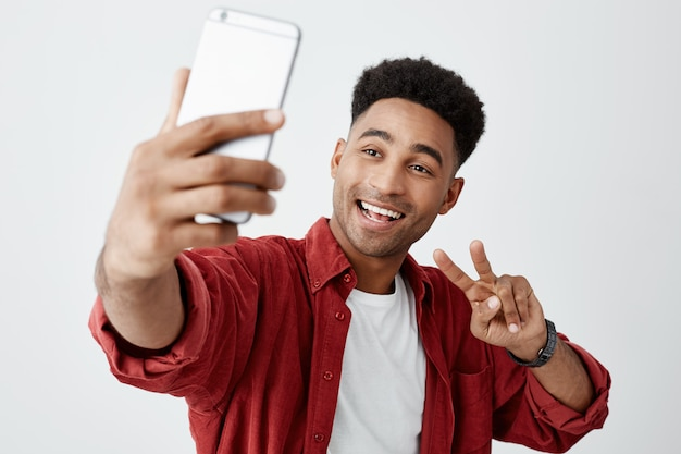 Портрет молодого привлекательного темнокожего африканского парня с вьющимися волосами в белой футболке и стильной красной рубашке, разговаривающей с подругой посредством видеовызова на сотовый телефон.