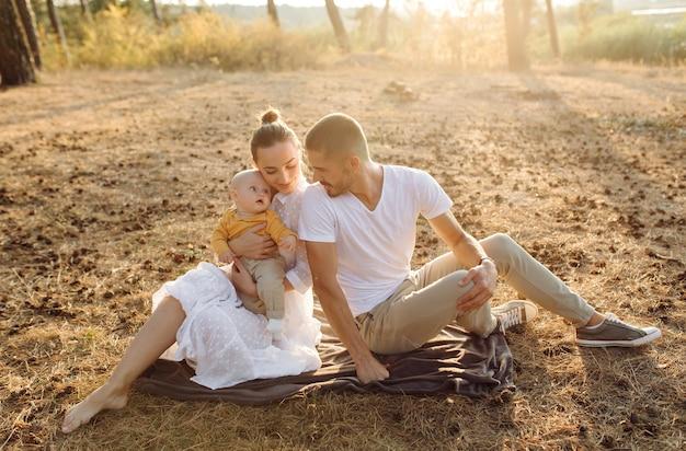 晴れた日に美しい秋の松林でポーズをとって、小さな赤ちゃんの息子と若い魅力的な家族の肖像画。ハンサムな男と彼のかなりブルネットの妻