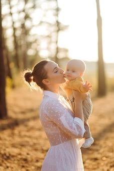 Портрет молодой привлекательной семьи с маленьким сыном, позирует в красивом осеннем сосновом лесу в солнечный день. красивый мужчина и его хорошенькая брюнетка жена