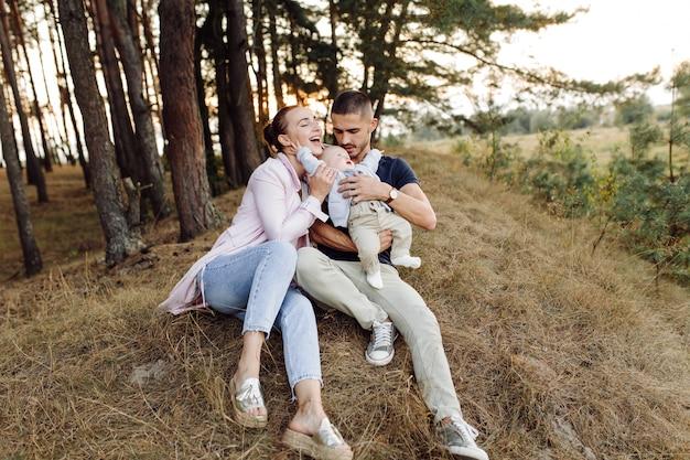 화창한 날에 아름 다운가 소나무 숲에서 포즈 작은 아기 아들과 함께 젊은 매력적인 가족의 초상화. 잘 생긴 남자와 그의 예쁜 갈색 머리 아내
