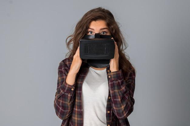 회색 배경 스튜디오에서 가상 현실 안경을 테스트하는 젊은 매력적인 소녀의 초상화