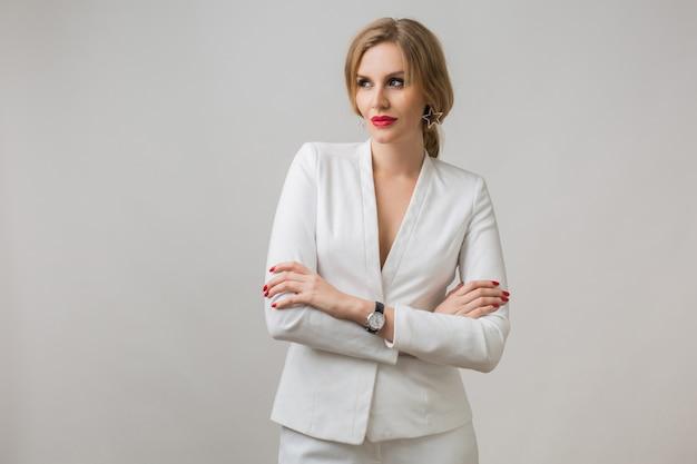 Портрет молодой привлекательной дамы в белом костюме, сексуальной и уверенной, независимой деловой женщины, элегантного стиля, красных губ, серьезного выражения лица, смотрящего в камеру, скрещенных рук, улыбки