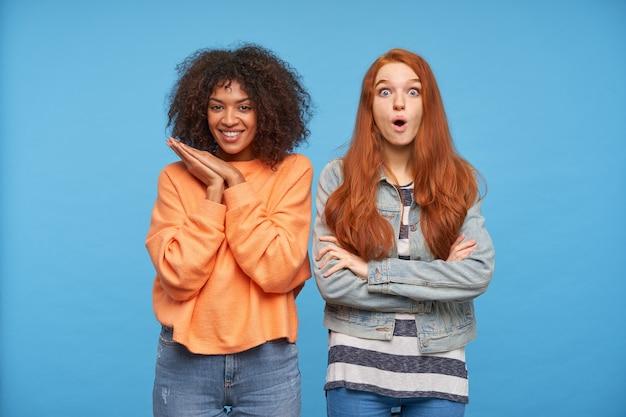 若い魅力的な長い髪の赤毛の女性の肖像画は、彼女の素敵な友人と青い壁の上でポーズをとって、手を組んで見ながら目を驚かせて丸くします