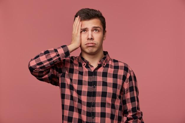 Портрет молодого привлекательного мужчины в клетчатой рубашке, смотрит вверх, стоит на розовом фоне и трогает голову, выглядит усталым и грустным.