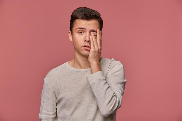 Портрет молодого привлекательного мужчины в белом с длинным рукавом, смотрит в камеру и касается лица, стоит на розовом фоне, выглядит усталым и грустным.