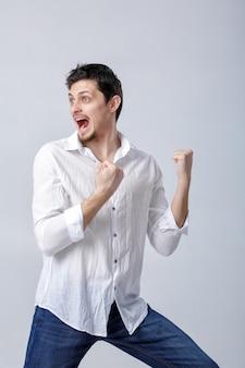 흰 셔츠에 검은 머리를 한 매력적인 젊은 남자의 초상화는 회색 배경에 머리 위로 손을 올립니다. 승자의 몸짓