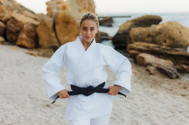 Портрет молодой привлекательной женщины мастера боевых искусств в белом кимоно с черным поясом на диком пляже