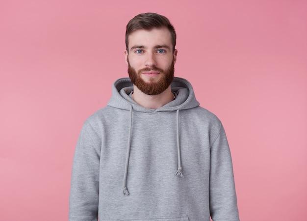 灰色のパーカーを着た若い魅力的な赤ひげを生やした男の肖像画は、ピンクの背景の上に立って、笑顔で、よく見えます。
