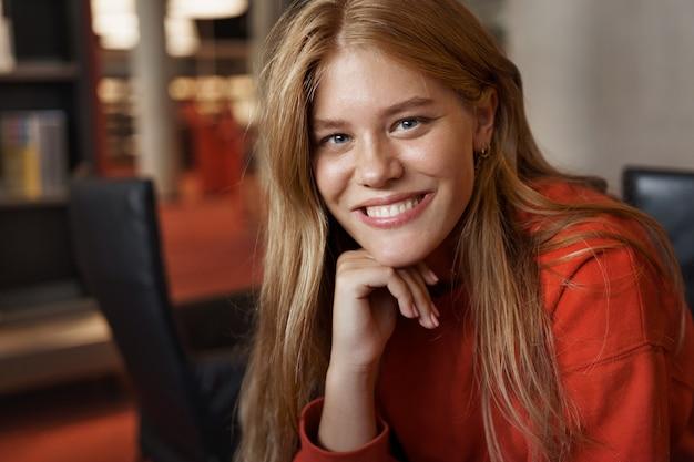 젊은 매력적인 빨간 머리 여성 학생의 초상화, 팔에 기대어 웃 고 안락의 자에 앉아있다.