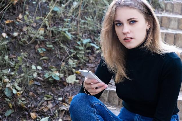 携帯電話を持って屋外の階段に座ってカメラを見ている黒いタートルネックの若い魅力的な深刻な青い目の女性の肖像画。