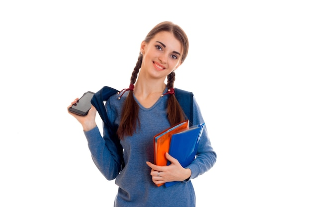 白い背景で隔離のバックパックとノートブックを持つ若い魅力的な学生の女の子の肖像画