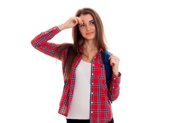 白い背景で隔離のバックパックを持つ若い魅力的な学生の女の子の肖像画