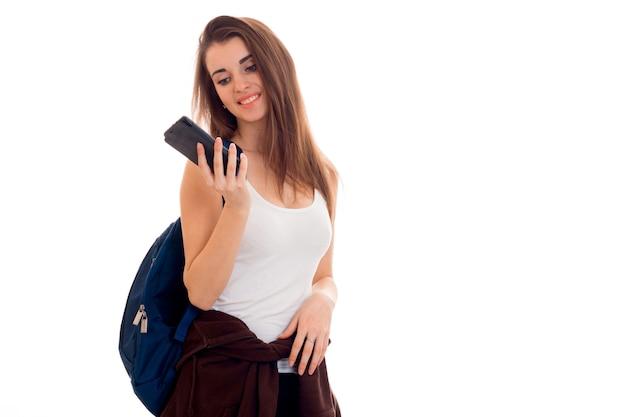 青いバックパックと白い背景で隔離の手に携帯電話を持つ若い魅力的な学生の女の子の肖像画