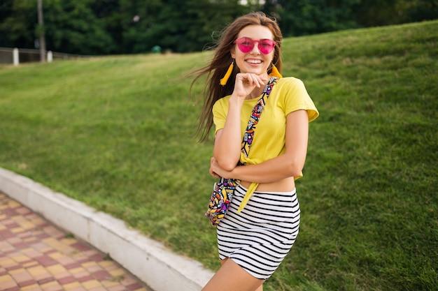 쾌활한 분위기, 긍정적 인 미소, 노란색 탑, 스트라이프 미니 스커트, 핸드백, 핑크 선글라스, 여름 스타일 패션 트렌드를 입고 도시 공원에서 포즈를 취하는 젊은 매력적인 세련된 여자의 초상화