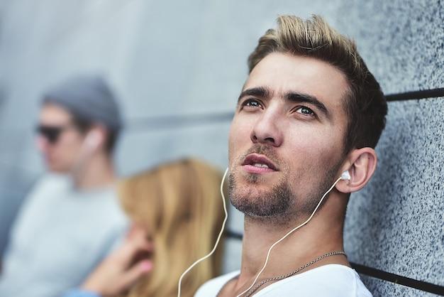 灰色の壁を背景にスタイリッシュな服を着て、同じヘッドフォンで音楽を聴いている若い魅力的な十代の若者たちの肖像画。