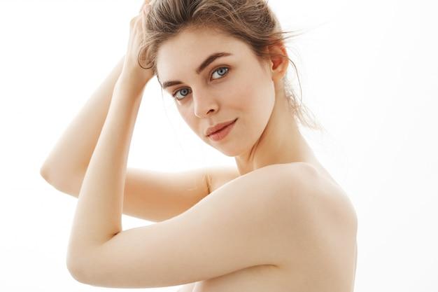 白い背景の上のパンと若い魅力的な柔らかい裸の女性の肖像画。