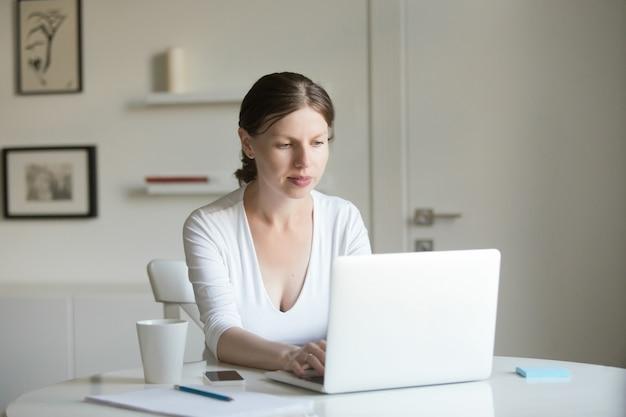 ラップトップと机の上で若い魅力的な女性の肖像