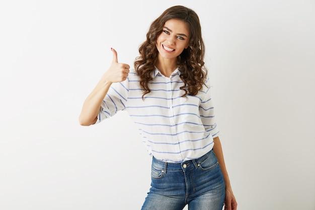 Портрет молодой привлекательной женщины, одетой в повседневную рубашку и джинсы, показывает позитивный жест, улыбается, счастливый, хипстерский стиль, изолированный, вьющийся, большой палец вверх, стройный, красивый,