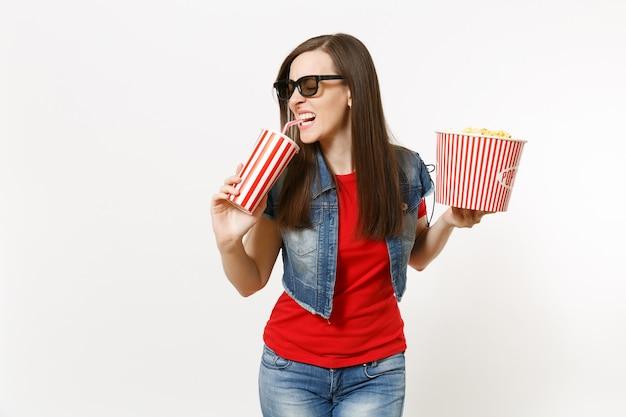 3d 안경을 쓰고 영화를 보고, 팝콘 양동이를 들고 흰색 배경에 격리된 플라스틱 컵에 소다나 콜라를 마시는 매력적인 젊은 여성의 초상화. 영화 개념의 감정.