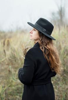 Портрет молодой привлекательной женщины в черном пальто и шляпе