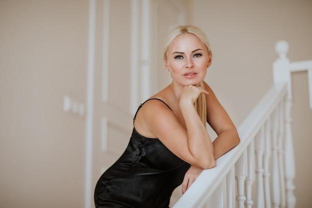 階段でポーズをとって黒いイブニングドレスの若い魅力的な女性の肖像画。