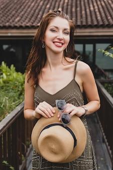 Портрет молодой привлекательной женщины в элегантном платье, соломенной шляпе, летний стиль, модная тенденция, отпуск, улыбка, стильные аксессуары, солнцезащитные очки, позирует на тропической вилле на бали