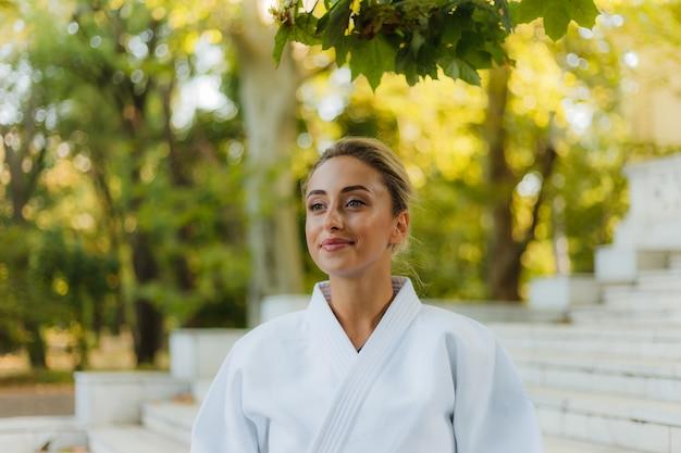 Портрет молодой привлекательной женщины в белом кимоно. спорт женщина на открытом воздухе. боевые искусства