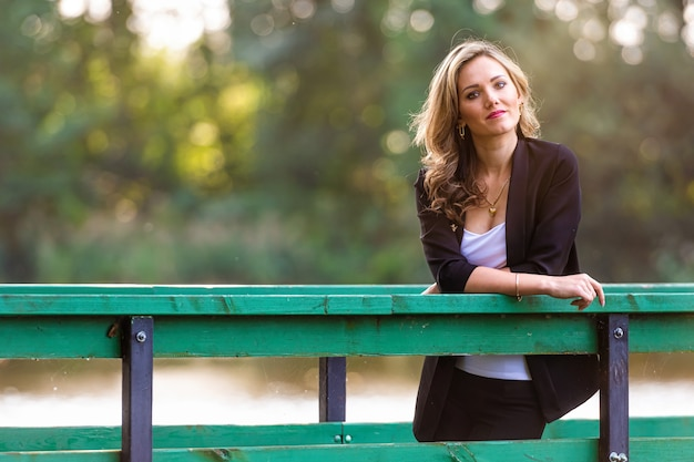 Портрет молодой привлекательной женщины, опирающейся на перила пешеходного моста и смотрит в камеру