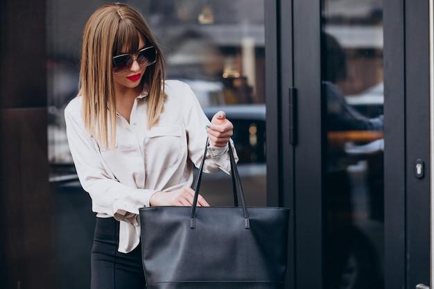 彼女のバッグを見ている若い魅力的な女性モデルの肖像画