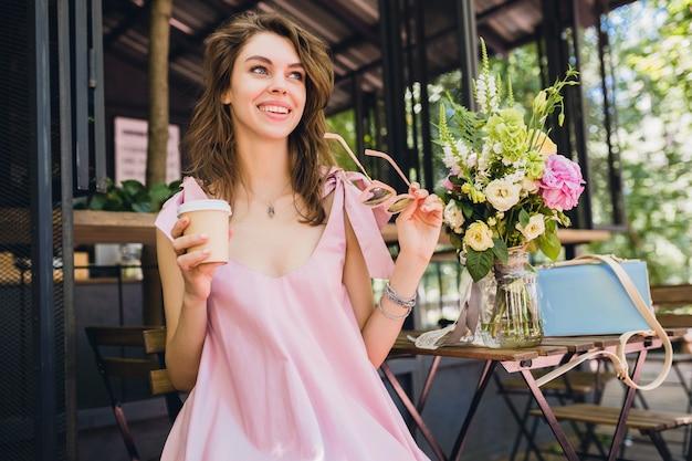 カフェ、夏のファッションの服、ピンクのコットンドレス、サングラス、笑みを浮かべて、コーヒーを飲んで、スタイリッシュなアクセサリー、トレンディなアパレル、幸せな気分に座っている若い魅力的な女性の肖像画