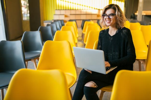 Портрет молодой привлекательной женщины, сидя в лекционном зале, работает на ноутбуке, в очках, классе с множеством желтых стульев, студентам, обучение онлайн, фрилансер, счастливый, улыбающийся