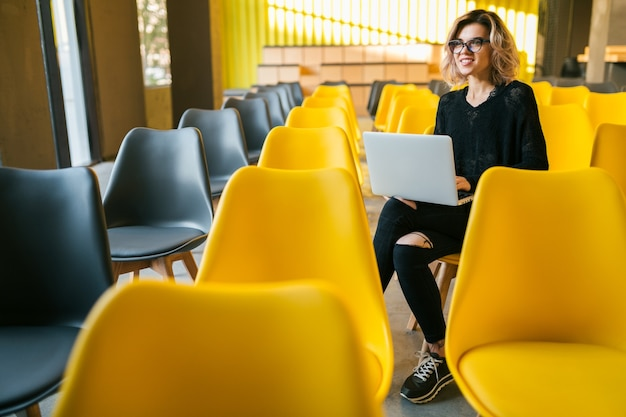 Портрет молодой привлекательной женщины, сидящей в лекционном зале, работающей на ноутбуке в очках, студента, обучающегося в классе с множеством желтых стульев