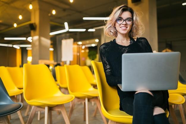 안경을 쓰고 노트북에서 일하는 강당에 앉아있는 젊은 매력적인 여자의 초상화, 많은 노란 의자가있는 교실에서 학습하는 학생