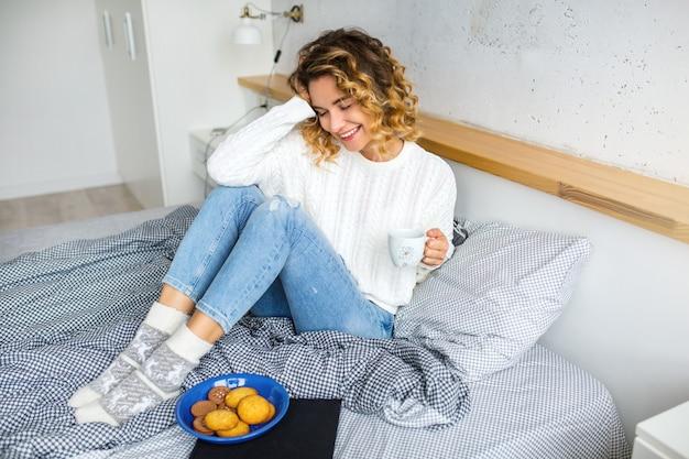 Портрет молодой привлекательной женщины, сидящей на кровати утром, пьет кофе в чашке, ест печенье