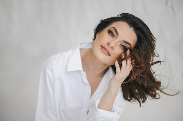 ヌードメイクとポジティブな感情とセクシーな視線と白い背景の上の明るい青い目をした若い魅力的な女性の肖像画