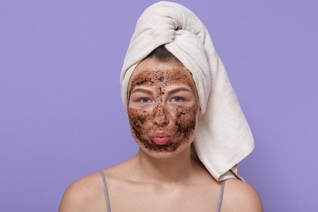 Портрет молодой привлекательной женщины с белым полотенцем на голове, позирует