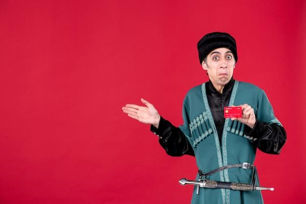 赤でクレジットカードを保持している伝統的な衣装で若いアゼルバイジャン人の肖像画