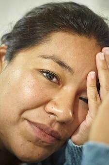 彼女の顔に手を持っている若い困惑したメキシコの女の子の肖像画