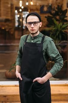 Портрет молодого бармена в черном фартуке.
