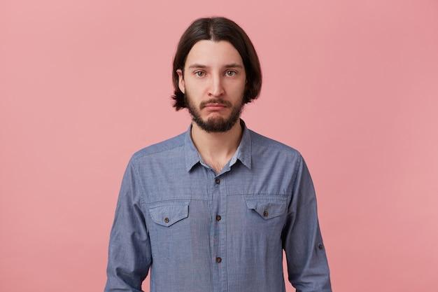 Портрет молодой бородатый брюнет обиделся, расстроен, подавлен, надул губы, в плохом настроении одет в повседневную рубашку, собирается плакать, изолирован на розовом фоне.