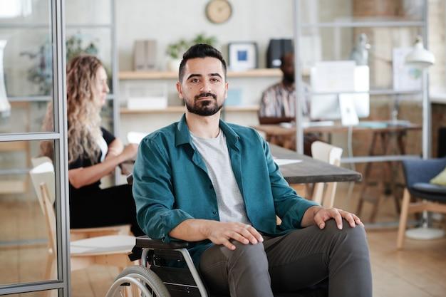 車椅子に座って、オフィスで働いている間カメラを見ている若いひげを生やしたビジネスマンの肖像画