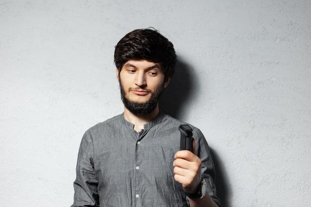 회색에 젊은 수염 난된 남자의 초상화는 그의 손에 면도 기계를보고 즐겁게.