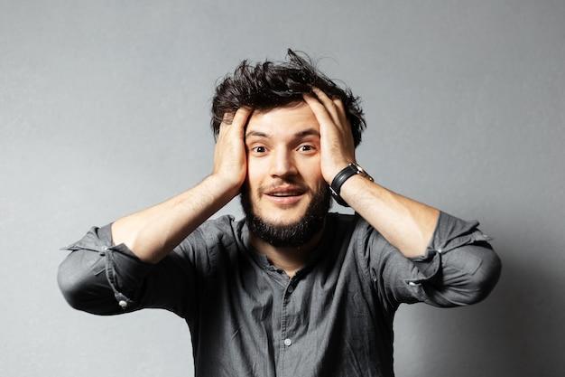 乱れた髪、驚いた表情を持つ若いひげを生やした男の肖像画は、頭に手を握っています。