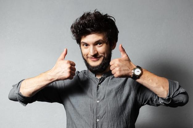 乱れた髪の若いひげを生やした男の肖像画は、灰色の上に親指を表示します。