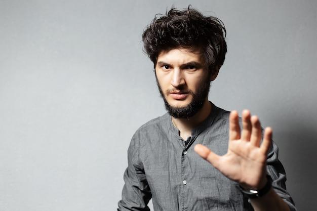 乱れた髪の若いひげを生やした男の肖像画は、灰色の腕をオンにしてジェスチャーstopを示しています。