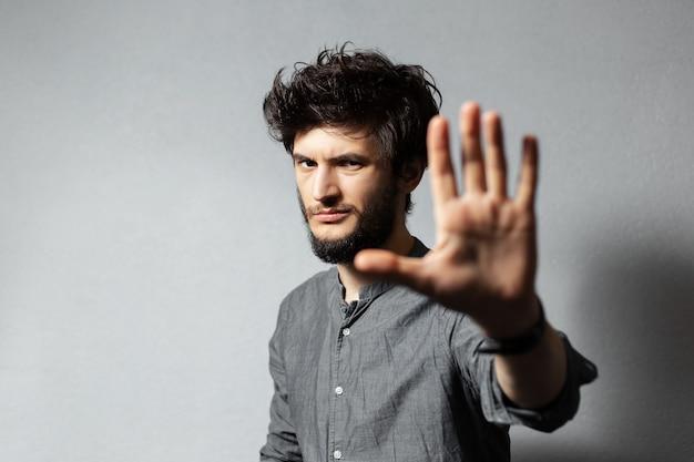 乱れた髪の若いひげを生やした男の肖像画は、灰色の手をオンにしてジェスチャーstopを示しています。