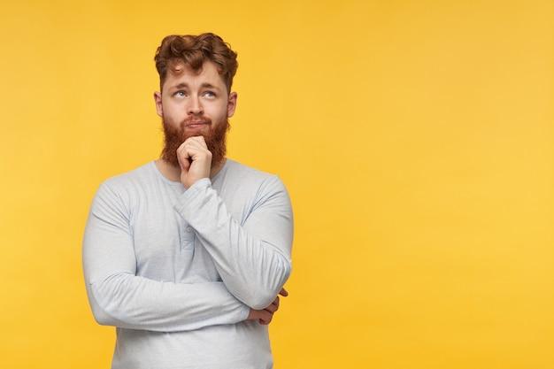 赤い髪の若いあごひげを生やした男の肖像画は、空白のtシャツを着て、コピースペースを慎重に脇に見て、黄色で彼のあごを強くします。